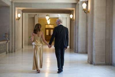 bride and groom walking hand in hand at City Hall