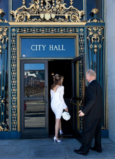 Groom holding the door for bride at City Hall in SF