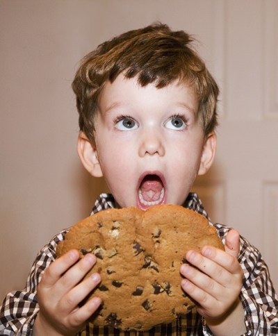 6-year-old boy eating a gigantic cookie