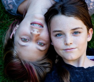 Two little girls heads next to each other looking at camera