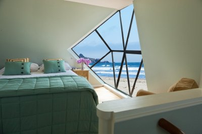 Interior shot of bedroom, window showing the beach