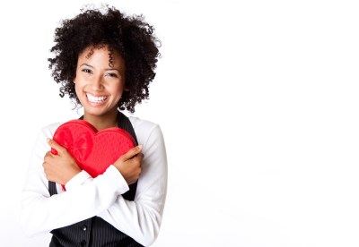 Happy woman with afro carrying red heart box