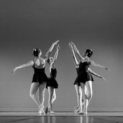 Black & white photo of four female ballet dancers dancing