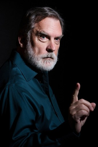 Serious man with grey beard gesturing - on black backdrop