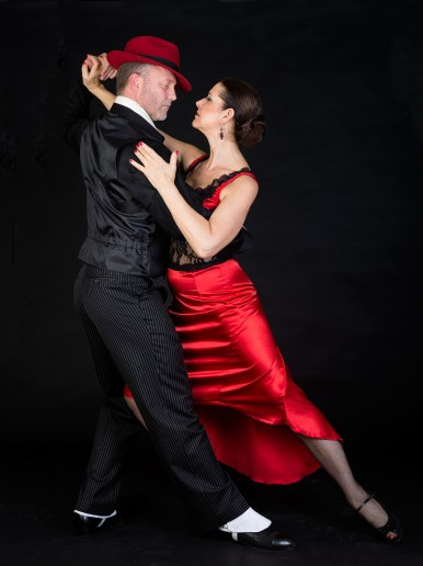 Couple dancing the tango on black background