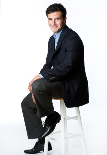 Full body shot of man sitting on stool