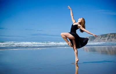 Ballet dancer in black dress dancing at the beach