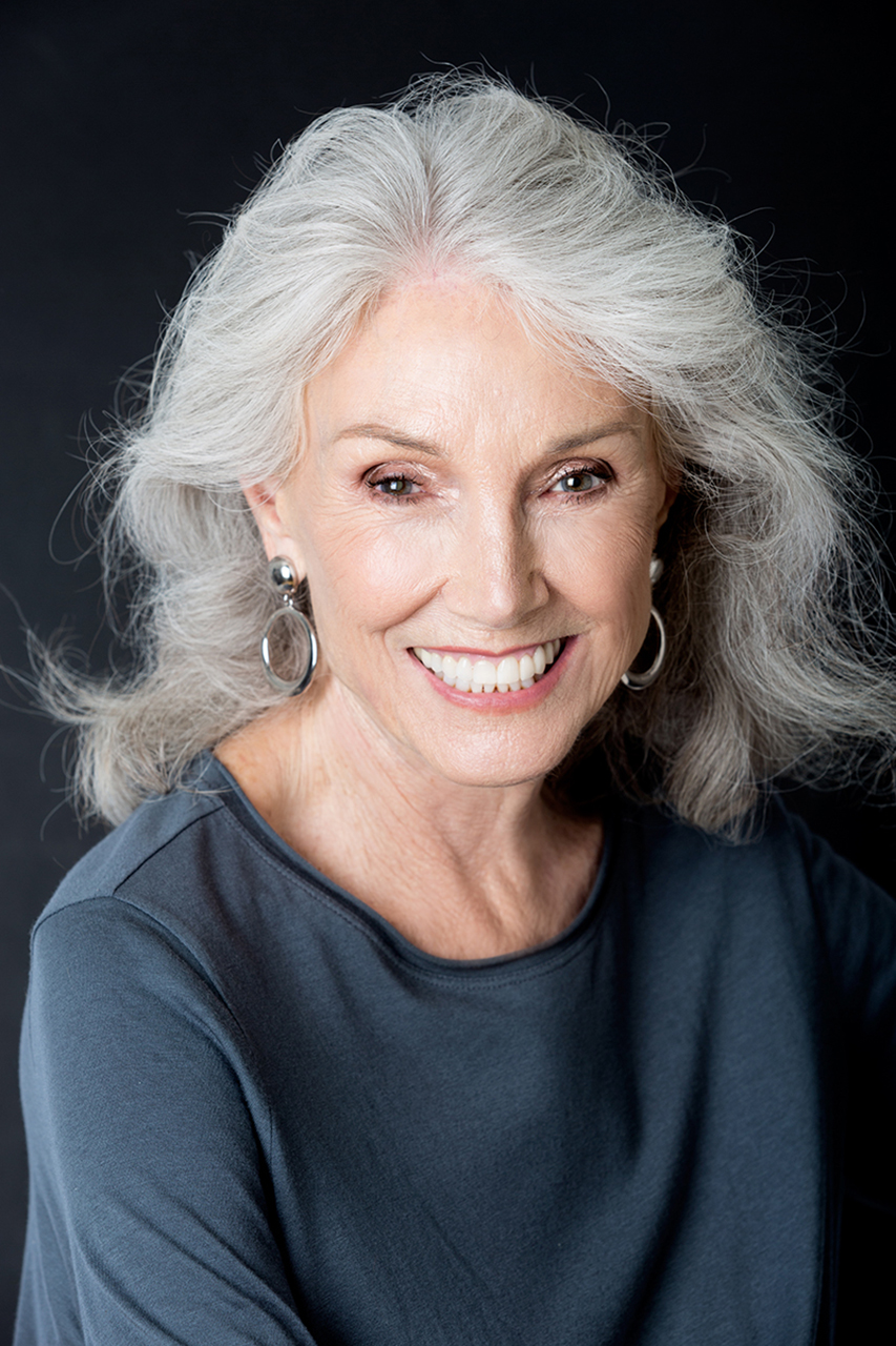 Headshot of older smiling woman with grey hair