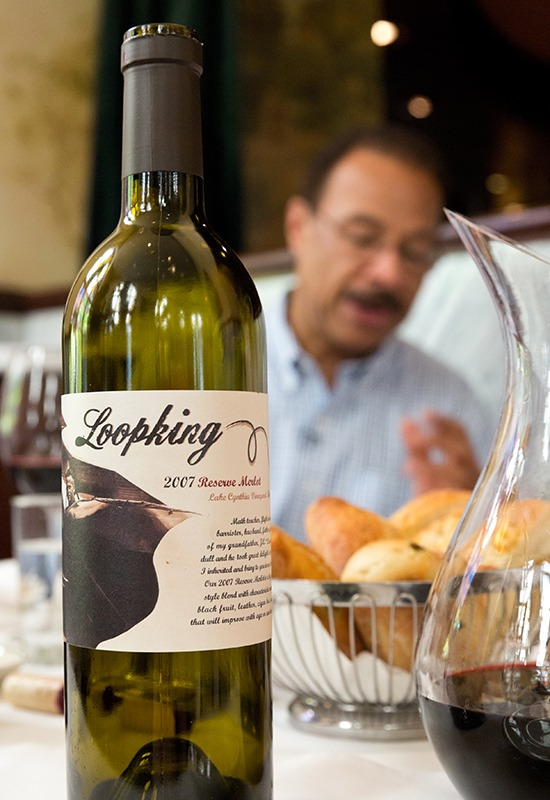 Closeup of wine bottle with Spencer Christian in back