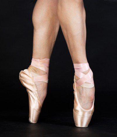 Female ballet dancer's feet standing on pointe