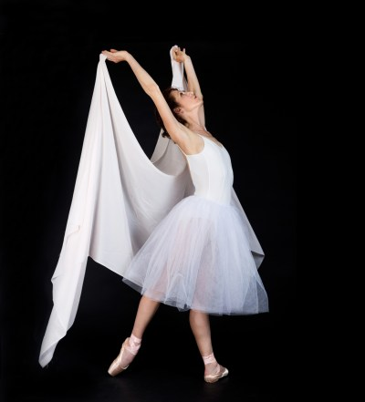 Female ballet dancer in white tutu on black background