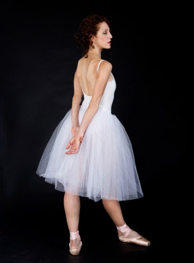 Female ballet dancer in tutu standing with arms behind her back