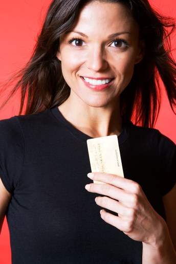 3/4 shot of woman with credit card on red backdrop