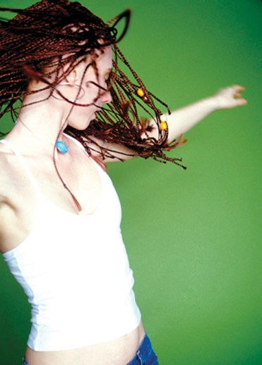 Young woman in dreads twirling on green background