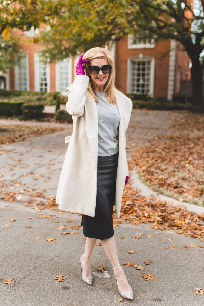 Tanya Foster wears a gray Zara sweater with pencil skirt, Jimmy Choo heels and a white wrap coat.