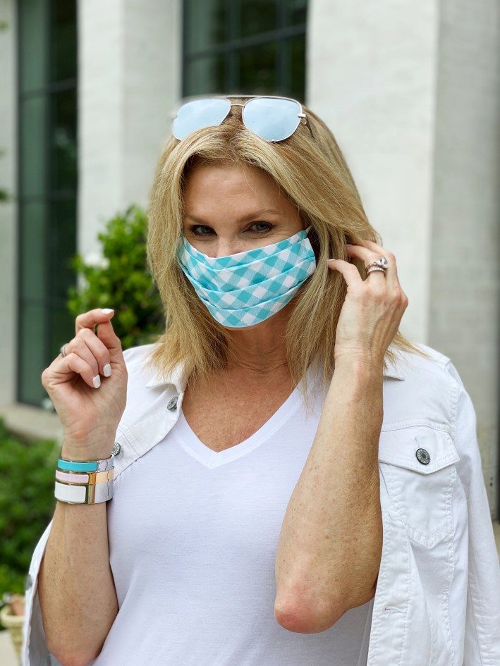 tanya foster in a white shirt and talbots white jean jacket with a face mask and hermes clic clac bracelets
