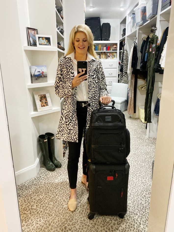 Animal print rain jacket, black pants, white shirt with Tumi luggage