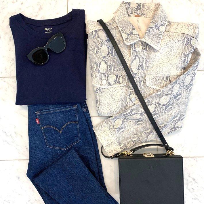 Snakeskin print denim jacket, blue tee, Levi's jeans and tde. crossbody bag