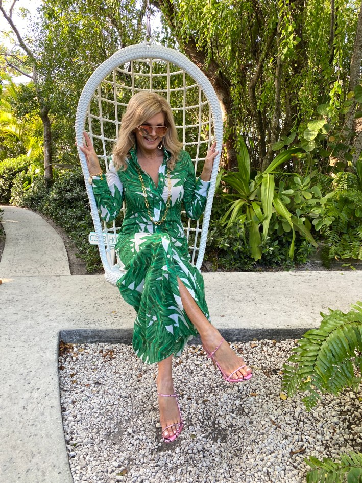 Tanya Foster sitting in a chair wearing palm print maxi dress