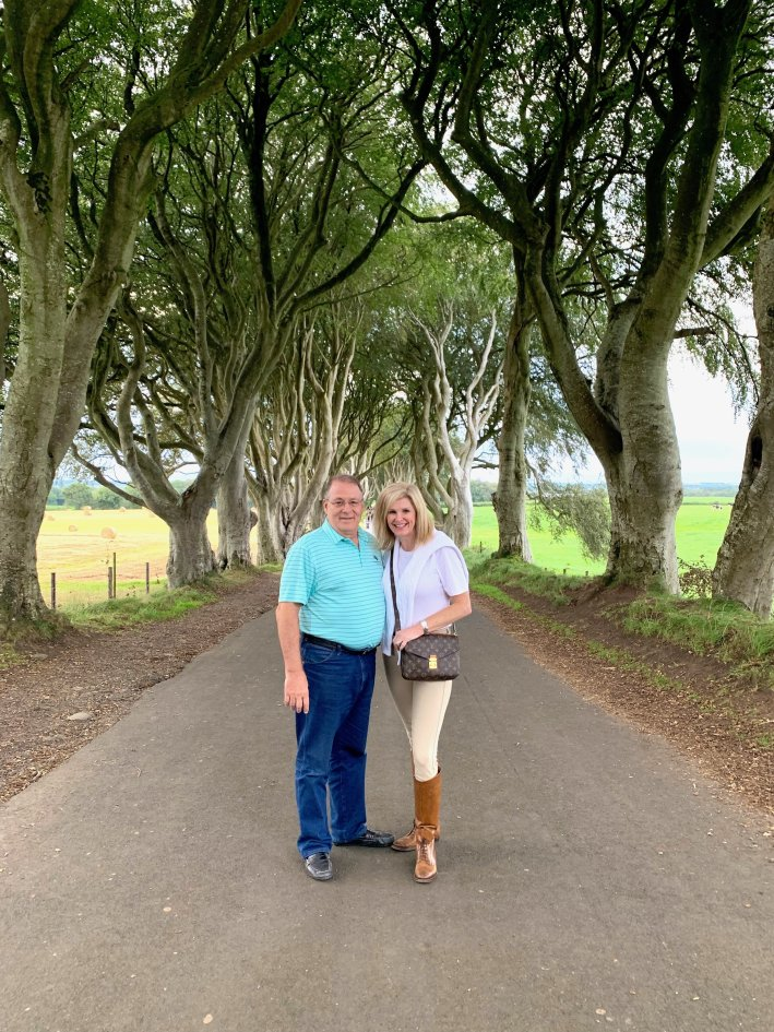 Game of Thrones location tour with Giant Tours | 8 Reasons to travel to Ireland now! by popular Dallas travel blogger, Tanya Foster: image of a man and a woman standing on a road under some tall trees.