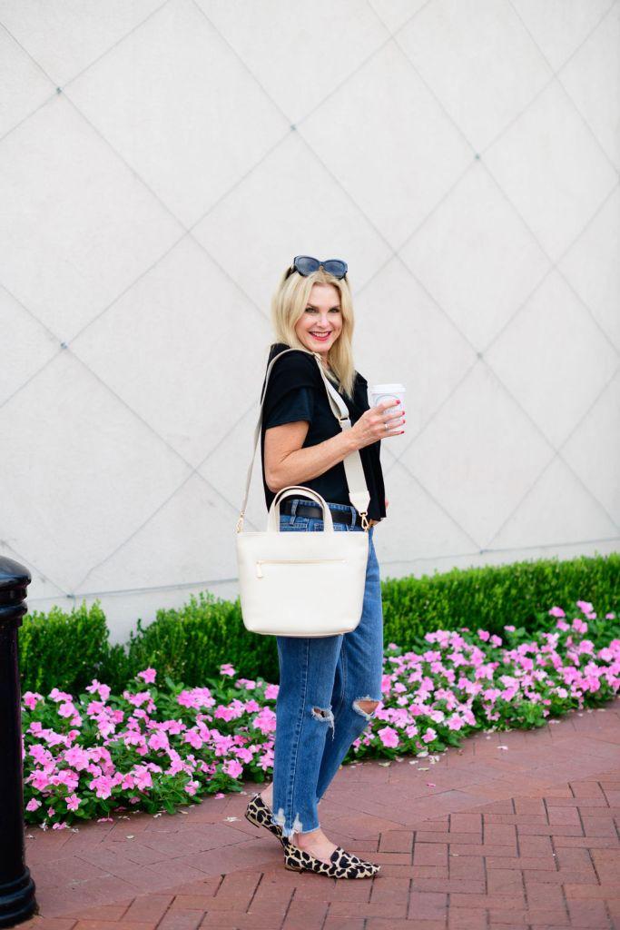 Tanya Foster wearing Avara jeans and top holding GiGi New York Marine satchel