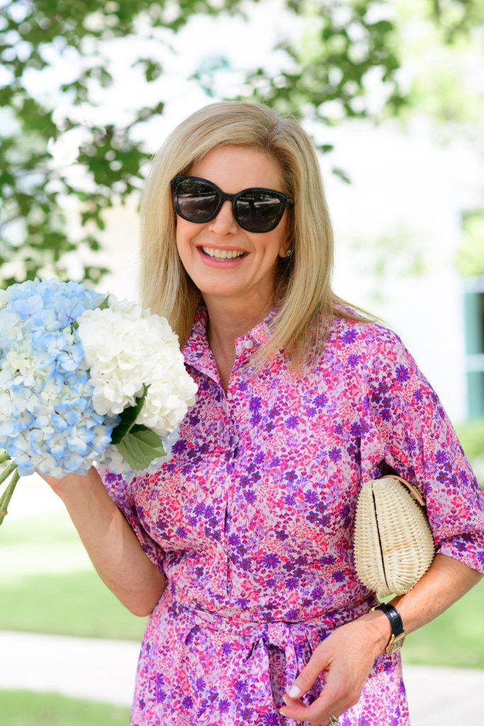 Tanya Foster in Tuckernuck pink floral betty dress holding flowers and tuckernuck clutch