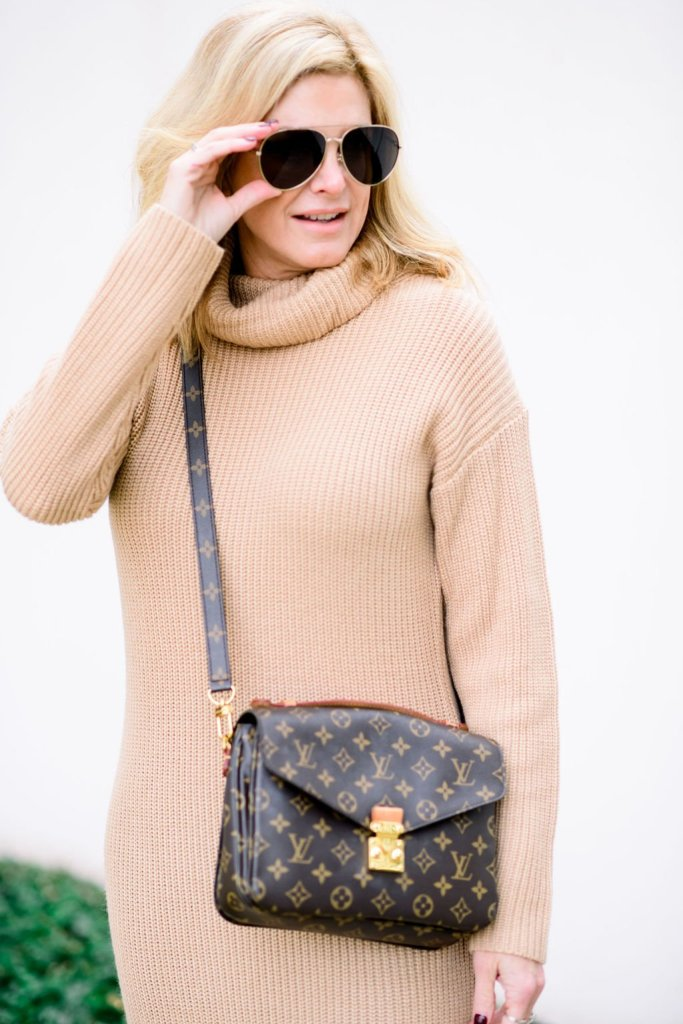 TAnya foster in a camel sweater dress and louis vuitton purse