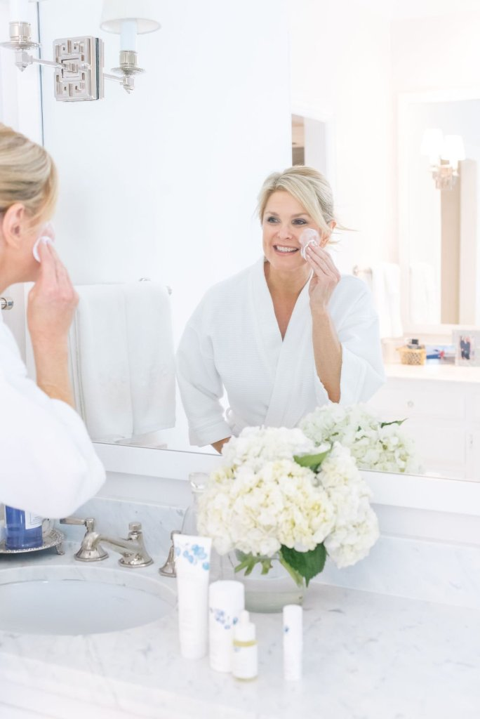 Mary Kay Naturally Product Launch | Introducing Mary Kay Naturally Collection by popular Dallas beauty blogger, Tanya Foster: image of a woman looking in her bathroom mirror and applying a Mary Kay Naturally product to her face.