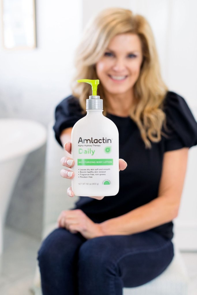 Tanya Foster holding a bottle of AmLactin Daily loction