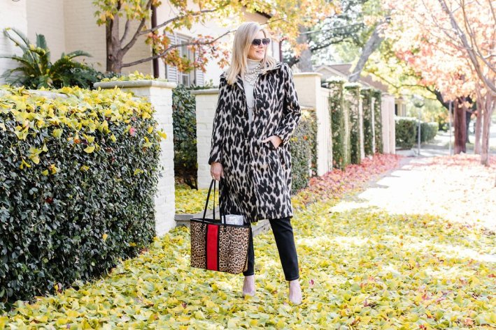 Tanya Foster standing on a sidewalk in an animal print Chico's coat