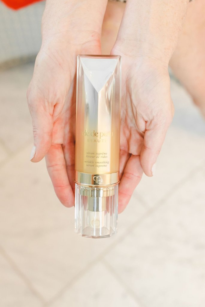 CLÉ DE PEAU WRINKLE SMOOTHING SERUM SUPREME | Product Review: CLÉ DE PEAU WRINKLE SMOOTHING SERUM SUPREME by popular beauty blogger Tanya Foster: image of a woman holding Clé de Peau Wrinkle Smoothing Serum Supreme