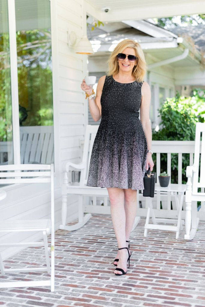 Day to night dresses - Eliza J   Best Day to Night Dresses by popular Dallas fashion blogger, Tanya Foster: image of woman standing outside on a porch and wearing an Eliza J Ombré Dot Fit & Flare Sweater Dress and black Stuart Weitzman Nudistsong Ankle Strap Sandals.