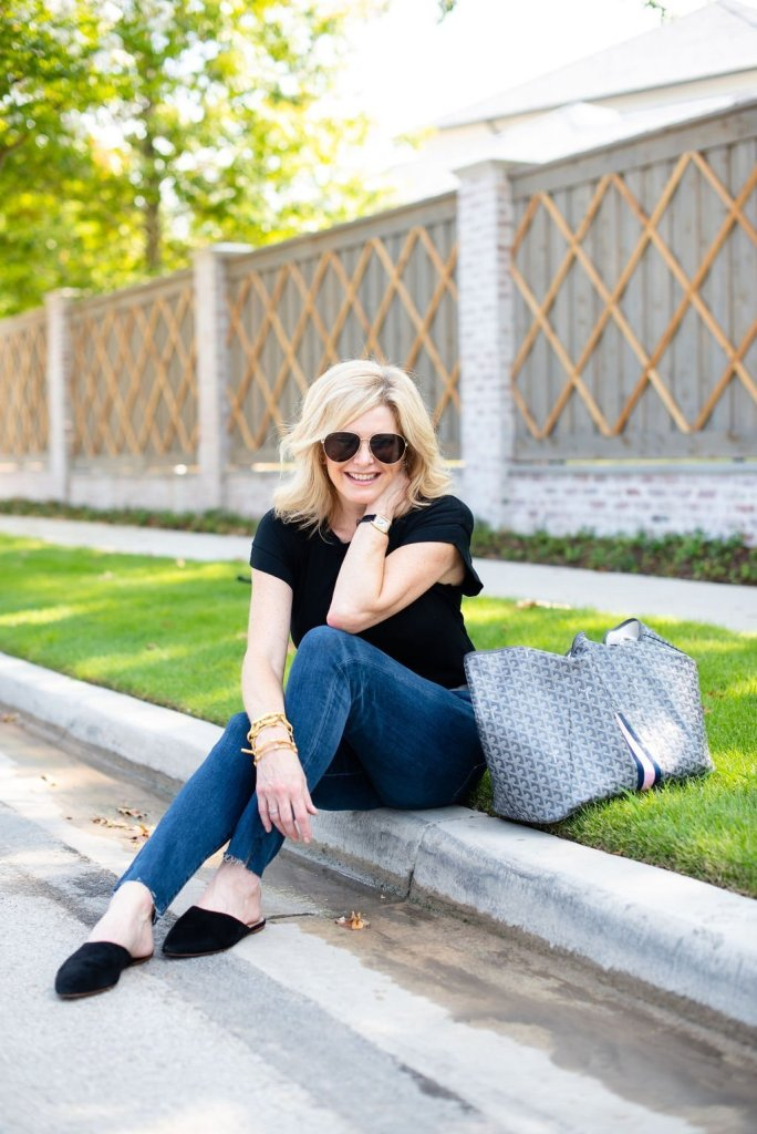 How to Wear a Black Tee 2 Ways by popular Texas fashion blogger, Tanya Foster: image of a woman sitting on a street curb and wearing a Madewell Northside Vintage Tee, AG The Farrah High Waist Ankle Skinny Jeans, Hermes belt, and Madewell Remi Mule.