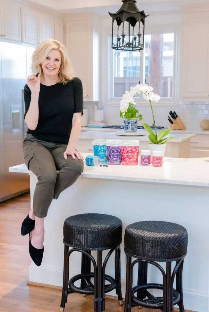 Why I love my Olly Vitamins! by popular life and style blogger, Tanya Foster: image of a woman sitting next to containers or Olly Vitamins on top of her kitchen island while holding an Olly Vitamin in between her fingers.