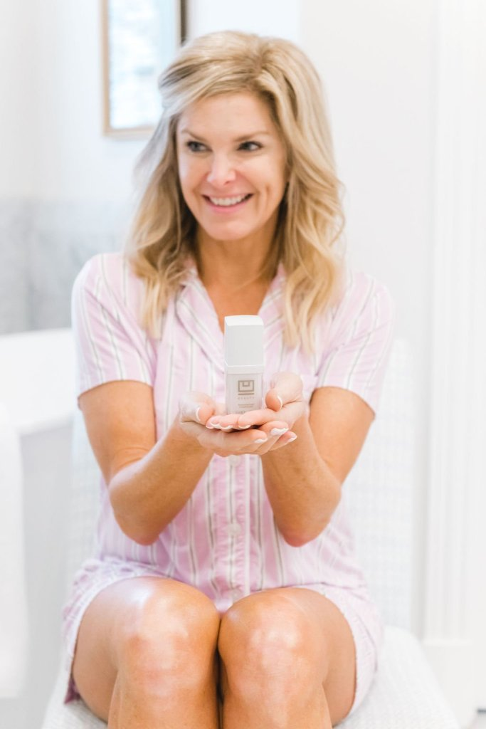 Tanya Foster holding a bottle of UBeauty