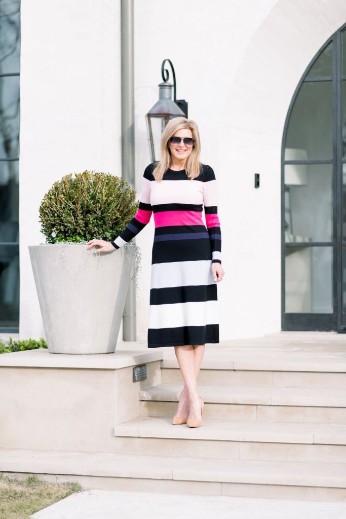 Tanya Foster standing on the steps in a striped Eliza J sweater dress