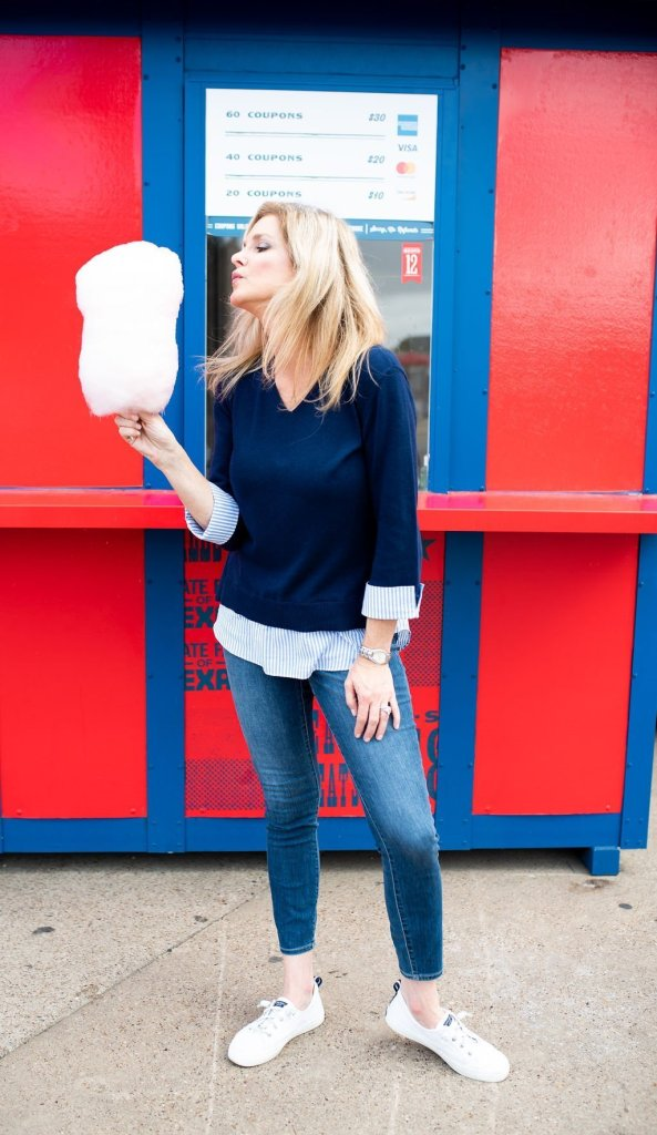 10 Things to do at the Texas State Fair! by popular Dallas blogger, Tanya Foster: image of a woman at the Texas State Fair holding some cotton candy.