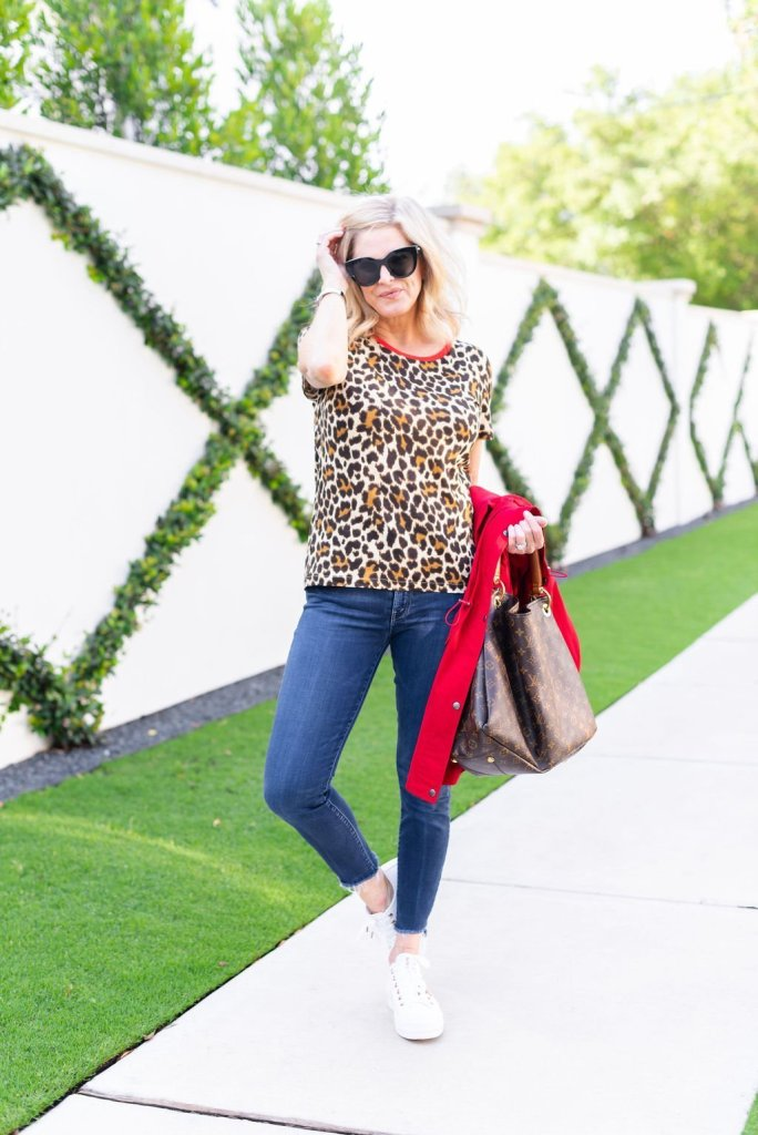Talbots red raincoat | Introduction to my Fall Fashion Favorites by popular Dallas fashion blogger, Tanya Foster: image of a woman wearing a red Talbots Hooded Anorak, leopard print tee, jeans, white sneakers, sunglasses, and holding a Louis Vuitton bag.