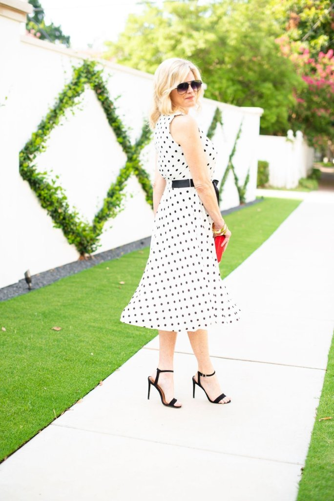 Twirling into Fall in Harper Rose midi dress | 3 Things to Look for in a Polka Dot Midi Dress by popular Dallas fashion blogger, Tanya Foster: image of a woman standing outside by a white wall and wearing a Nordstrom Harper Rose Polka Dot Fit & Flare Dress, black stiletto heel sandals, sunglasses, and holding a red clutch.