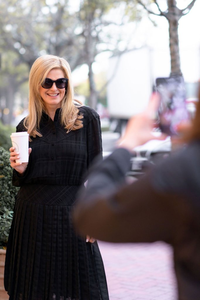 Tanya Foster in a Coach dress and sunglasses holding coffee and posing for a picture