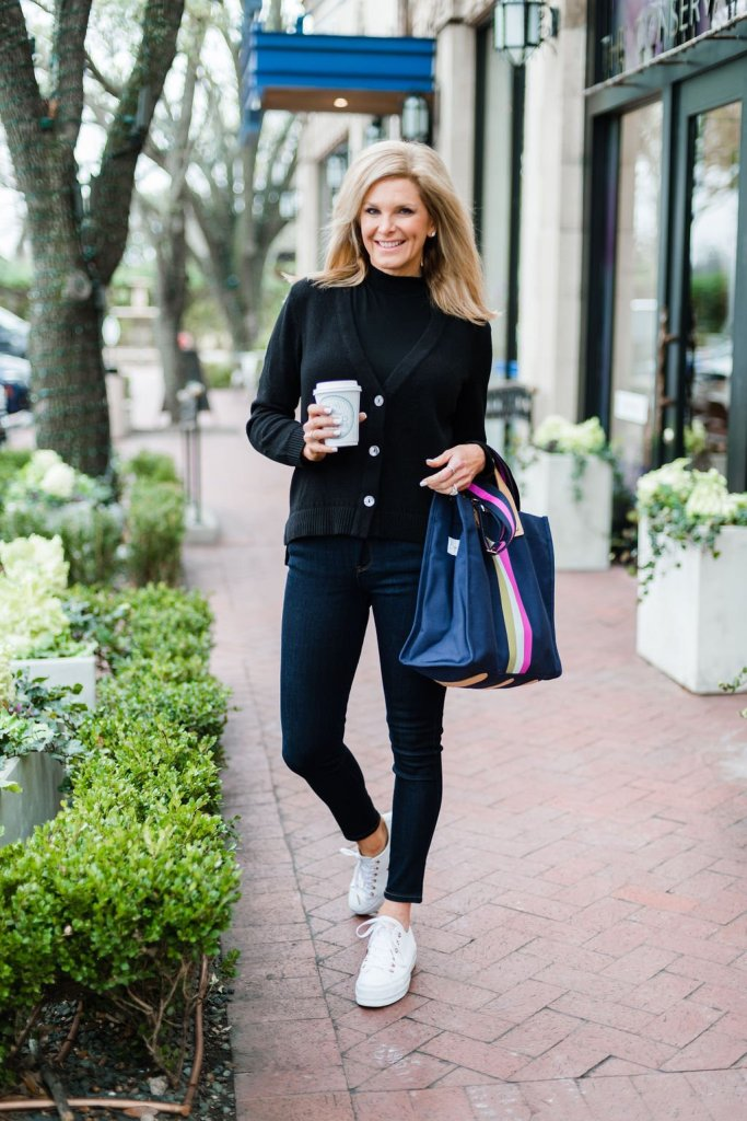 Tanya Foster standing on a sidewalk in a chico's black cardigan with a Madewell black mock neck shirt and mott & bow denim jeans with a bagging rights tote-ally bag