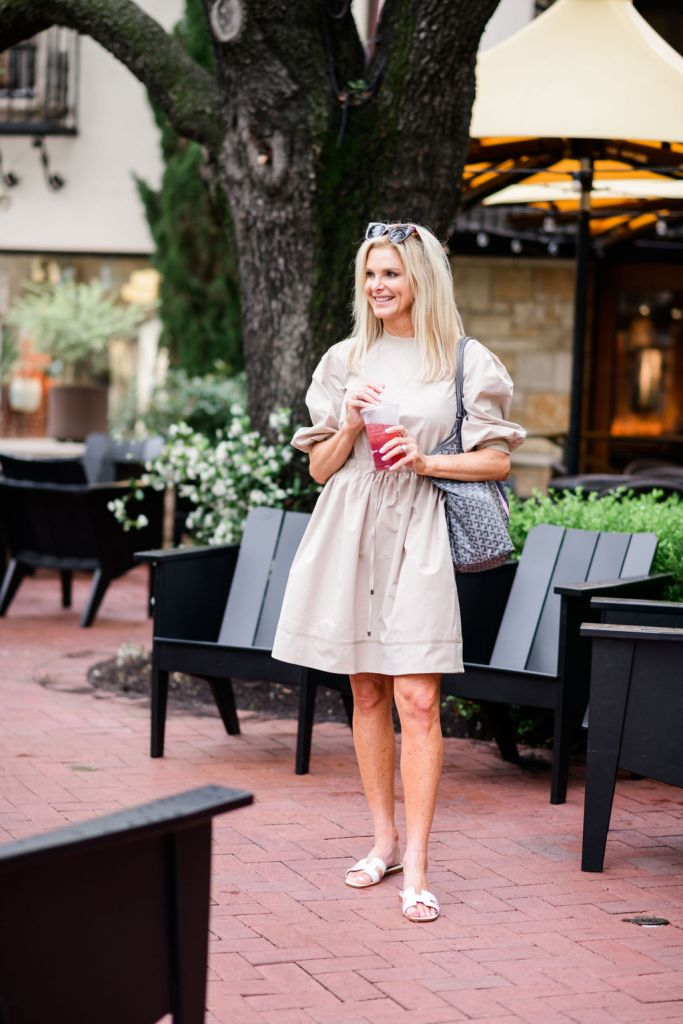 Tanya foster wearing beige dress with barrington tote and tuckernuck sunglasses and slide sandals