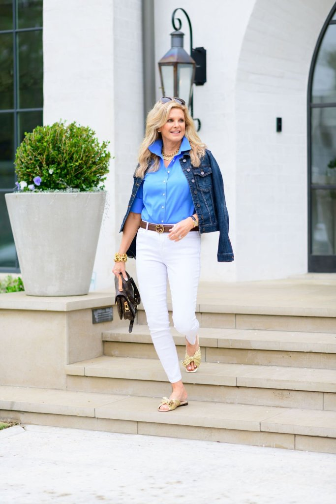 Tanya Foster standing on a step in white jeans gucci belt shopbop shoes a jean jacket and louis vuitton crossbody purse