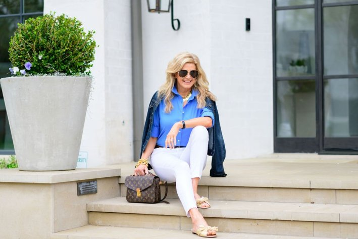 Tanya foster sitting on the steps in white jeans talbots blouse jean jacket shop bop shoes and a louis vuitton crossbody purse