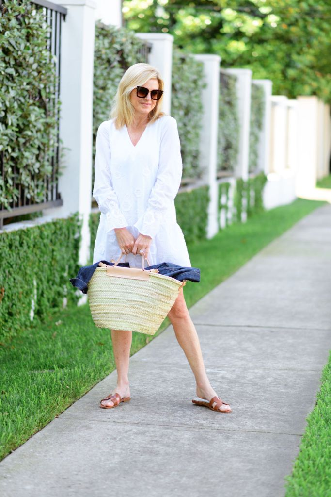 Tanya Foster wearing white embroidered dress with a straw bag and brown hermes sandals