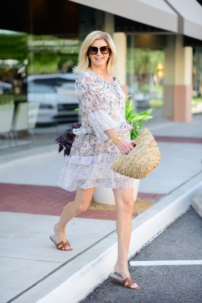 Tanya Foster walking in hale bob dress and odp bag and hermes oran sandals