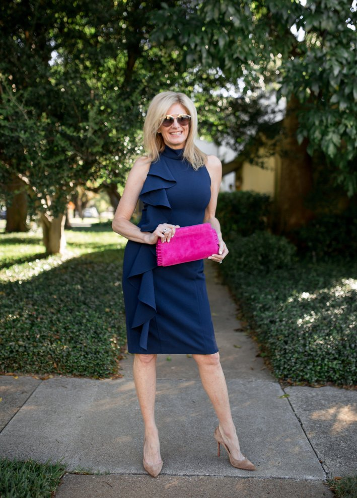 Eliza J blue sleeveless dress with ruffle and a hot pink suede clutch bag.