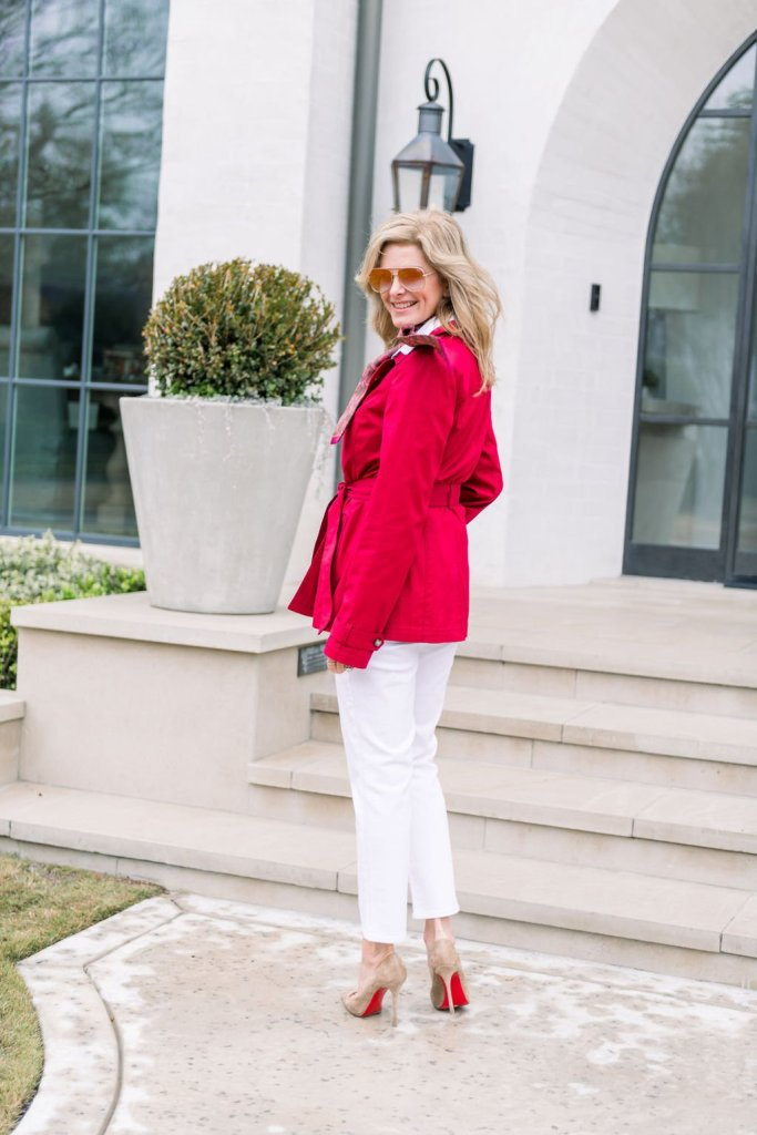 Tanya Foster wearing Talbots red trench coat, white jeans and white blouse with Christina Louboutin suede pumps