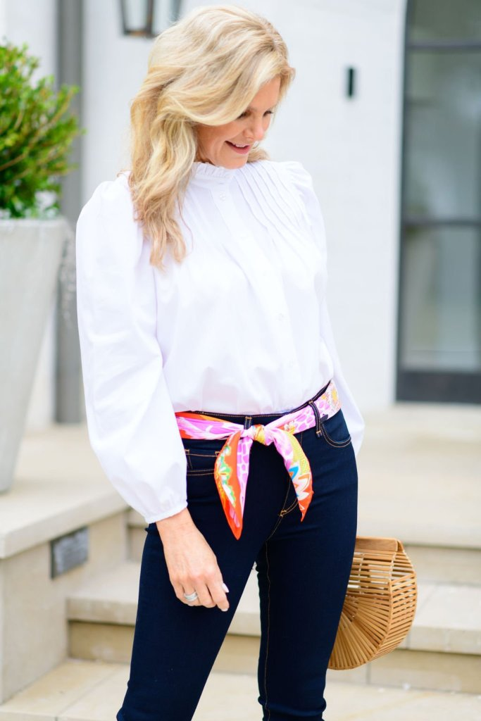 Tanya Foster standing in Veronica Beard jeans hermes scarf belt and a MANGO blouse