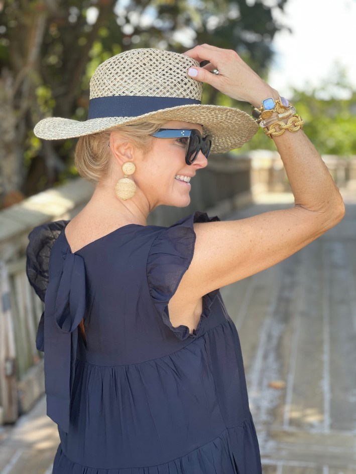 tanya foster holding avara hat and wearing avara maxi dress with tuckernuck earrings